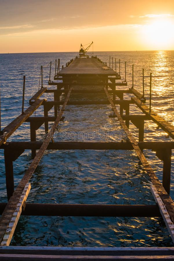 Disassembled old pier for ships over the sea at sunset. stock images