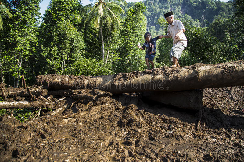Disaster in Banten. Banten, 26 July 2016. Residents back to their village checking on their belongings, they have to cross mud flows that almost 1,5 metres deep stock photos