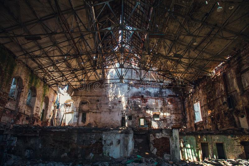 Disaster concept, inside old ruined abandoned industrial factory building, large creepy hall interior. Demolition and horror atmosphere, toned stock photos