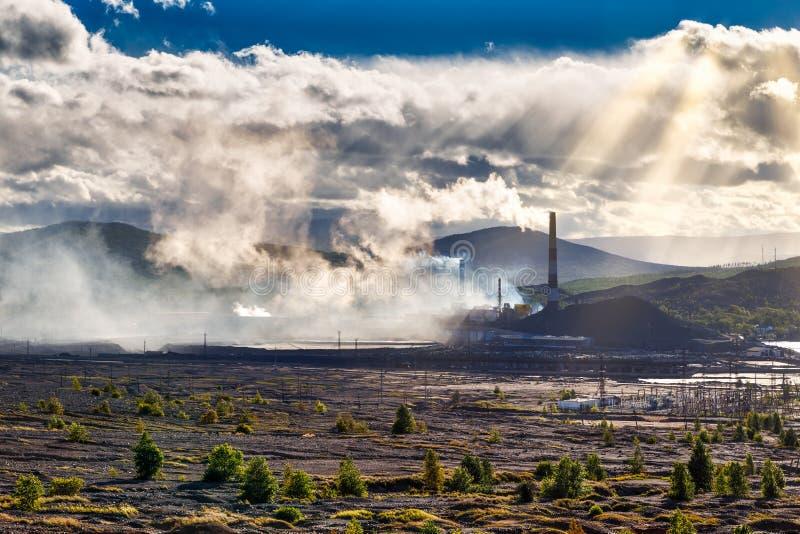 Disastro ambientale Pianta di rame in valle contro lo sfondo delle montagne, fumo tossico dai tubi, pioggia drammatica fotografia stock