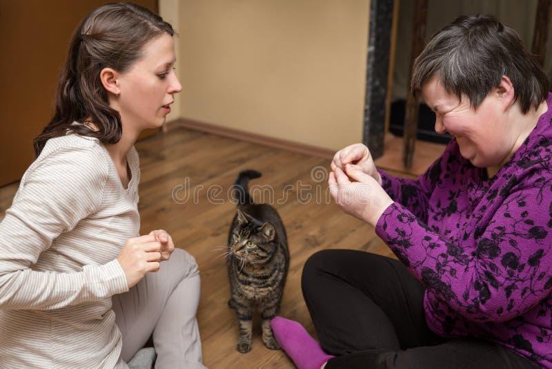 Disattiva mentalmente la donna e l'infermiere con un gatto, animale assistito immagini stock libere da diritti