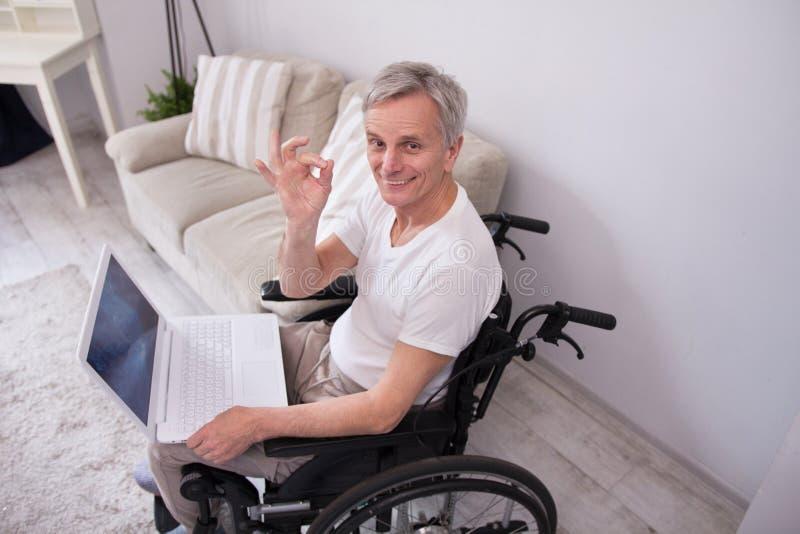 Disbaled-Mann, der Laptop verwendet stockfotografie