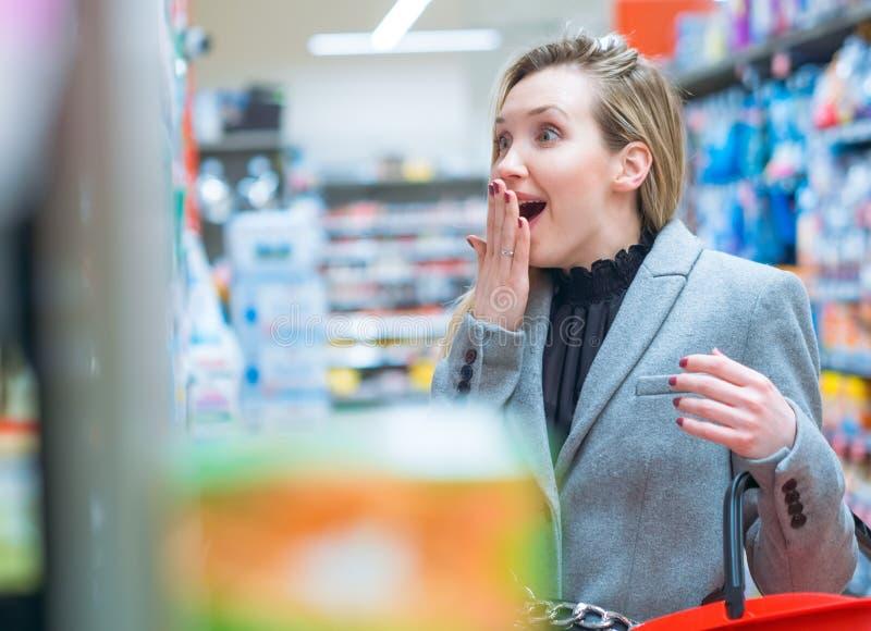 disbelief Mulher surpreendida no supermercado imagens de stock royalty free