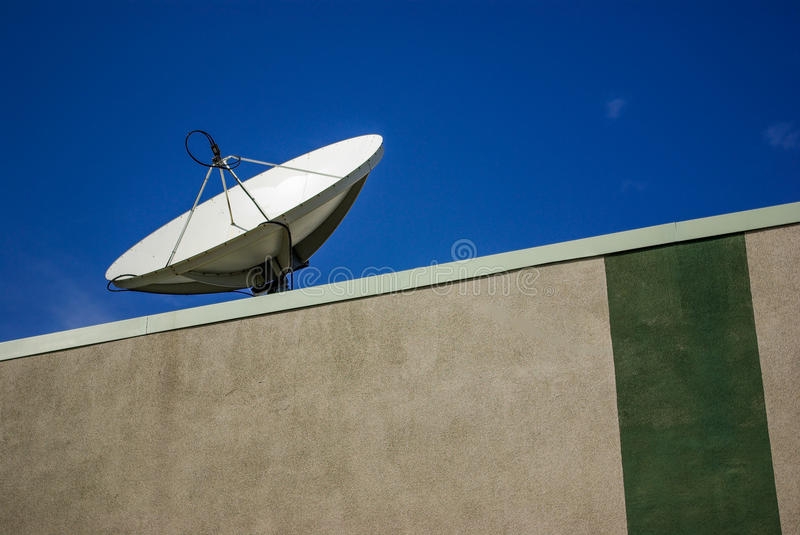 Disc Antenna. A disc antenna on the roof of a building capturing satellite signal stock images