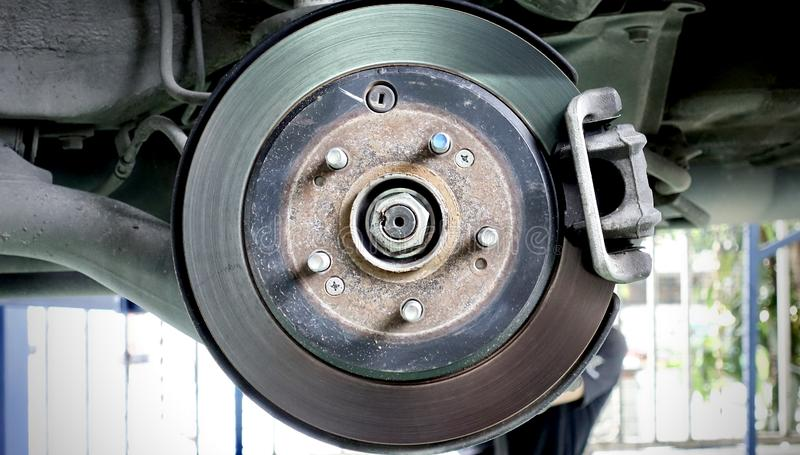 Disc brake of the vehicle for repair, in process of new tire replacement. Car brake repairing in garage. royalty free stock photos