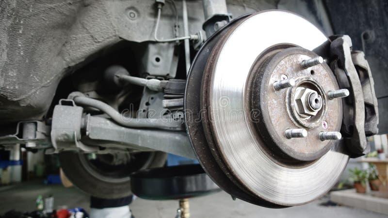 Disc brake of the vehicle for repair, in process of new tire replacement. Car brake repairing in garage. stock photo