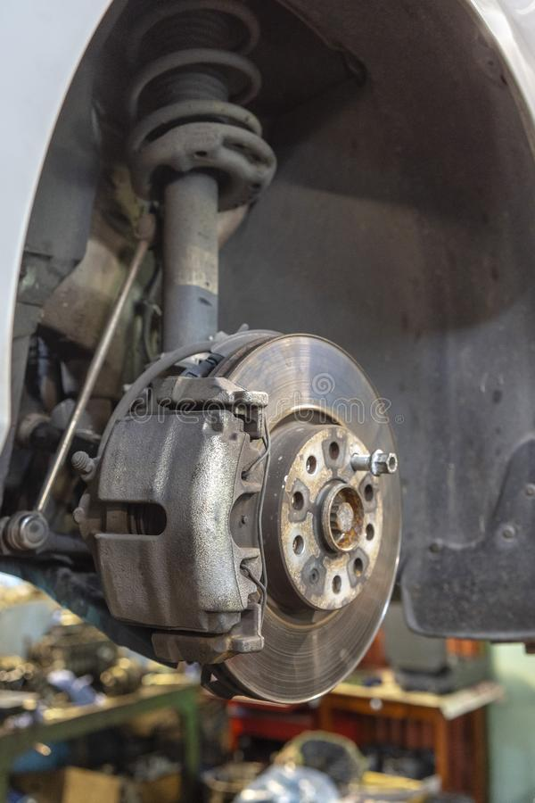 Disc brake of the vehicle for repair, in process of new tire replacement. Car brake repairing in garage.Close up. royalty free stock images