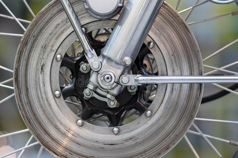 Disc brake wheel mecahnics. Motorbike mechanical engineering in. Close-up. Steel, chrome and aluminium engineered bike parts. Abstract design and technology stock photo