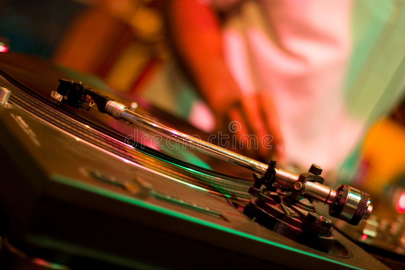 Disc jockey. A disc Jockey and his turntable at a dance club royalty free stock photo