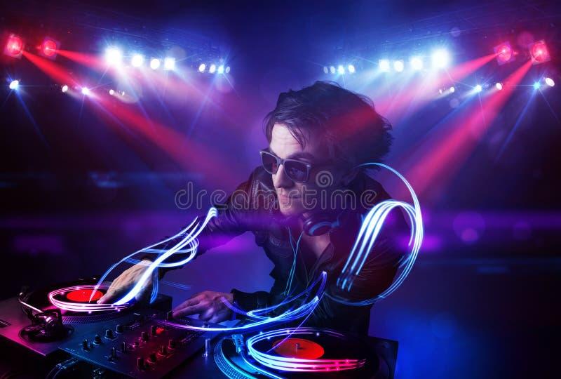 Disc jockey que juega música con efectos del haz luminoso sobre etapa foto de archivo libre de regalías
