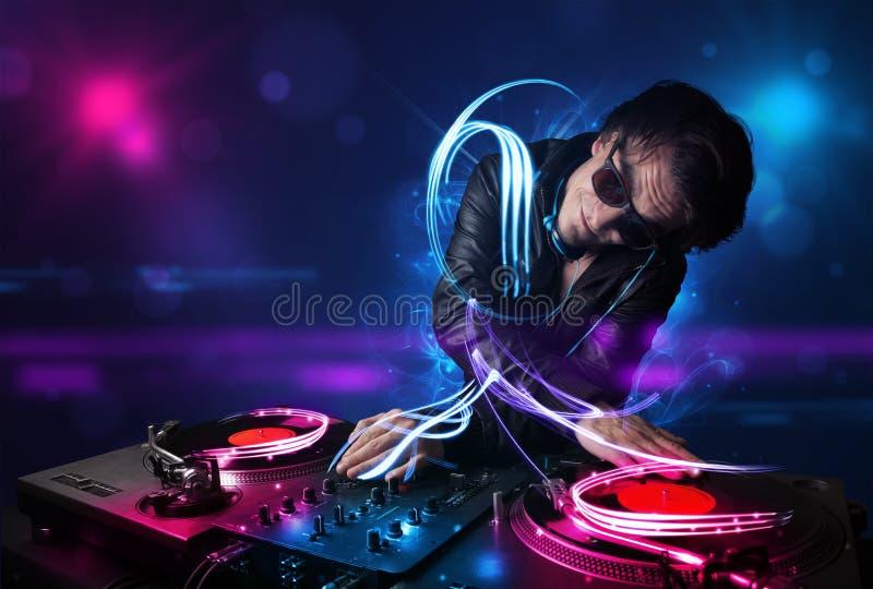 Disc jockey que juega música con electro efectos luminosos y luces foto de archivo