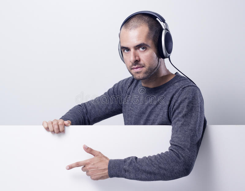 Disc jockey under blank banner and showing on it royalty free stock image