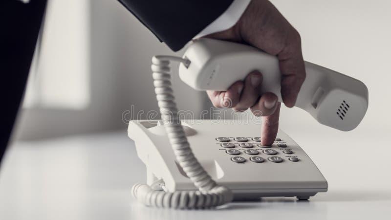 Discando um número de telefone em um dispositivo branco clássico da linha terrestre fotos de stock royalty free