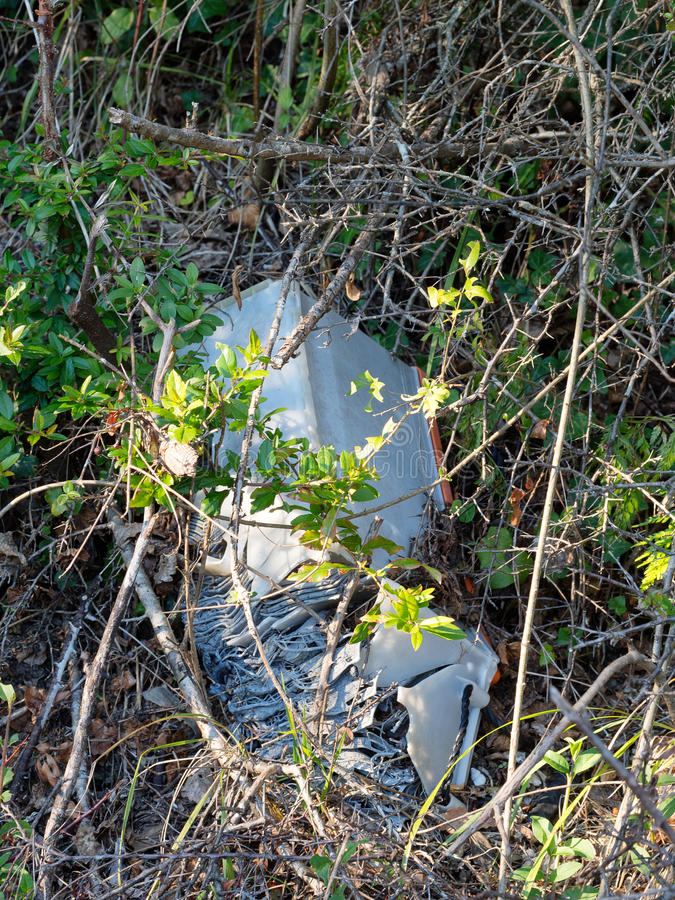 Discarded old car battery falling apart in hedge. Enviromental p. Illegal dumping .Enviromental pollution. Lead acid battery stock images