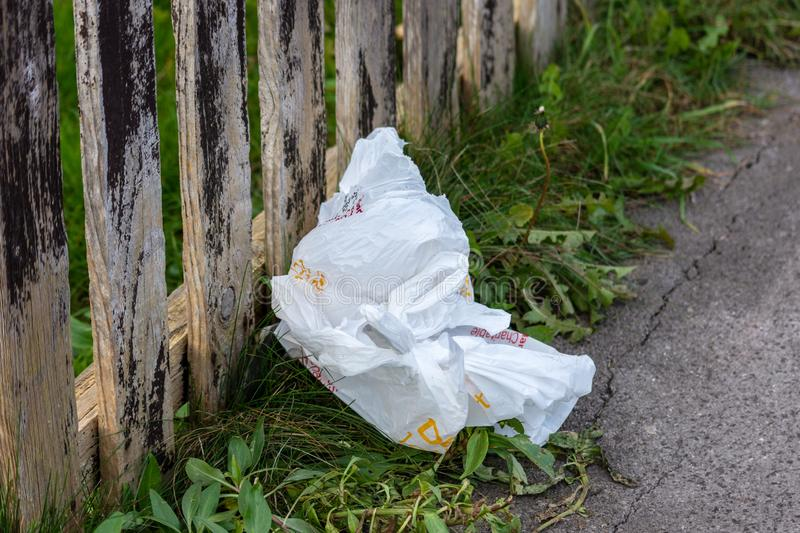 Plastic carrier bag thrown away as rubbish. A discarded single-use plastic carrier bag on a grass verge against a wood slat fence stock photo