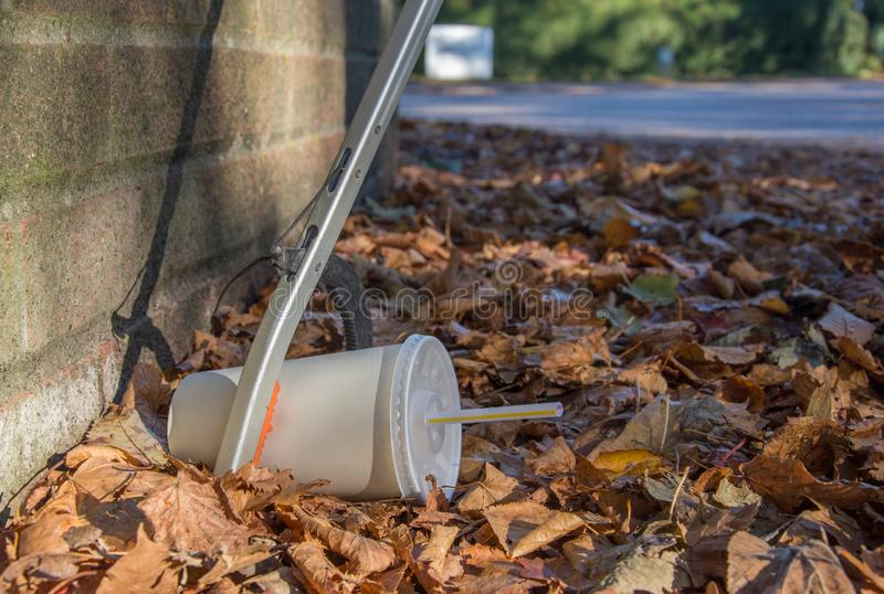 Discarded soda cup with straw in fallen leaves at the base of a wall. A litter picker uses a tool to retrieve a discarded soda cup that lies amongst fallen royalty free stock photos