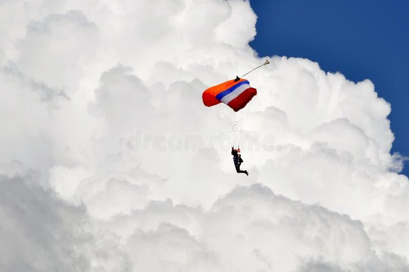 Discesa del paracadutista con il fondo bianco lanuginoso della nuvola fotografia stock libera da diritti