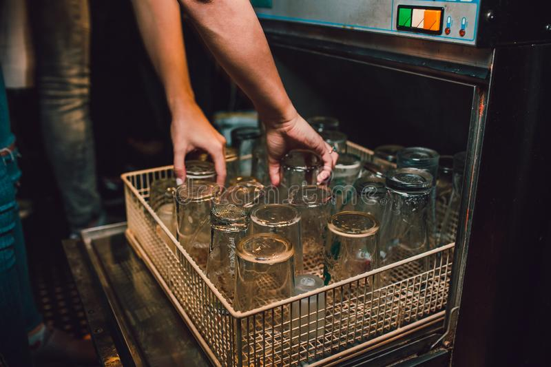 Discharging clean and shiny glasses from the dishwasher. stock photos