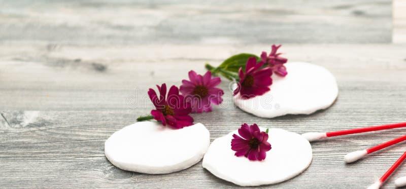 Dischi del cotone su un fondo bianco con i fiori Mezzi naturali del cosmetico per cura di pelle del fronte e del corpo Fuoco sele fotografia stock