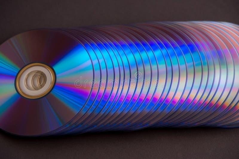 dischi del dvd e di deviazione standard su un fondo scuro grande pila immagini stock libere da diritti