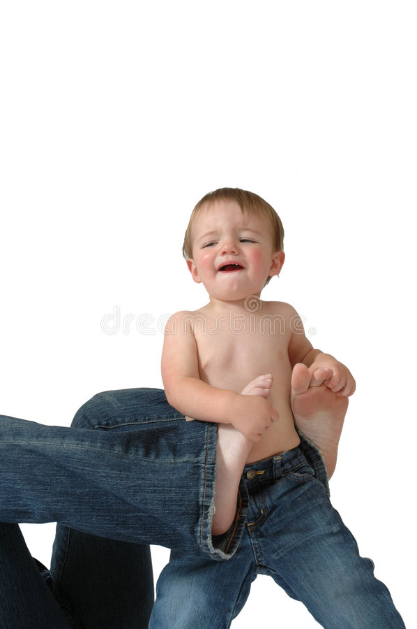 Discipline. A mother tries to keep her infant under control by wrapping her feet around him as he struggles to get away. Can be playful or not royalty free stock images