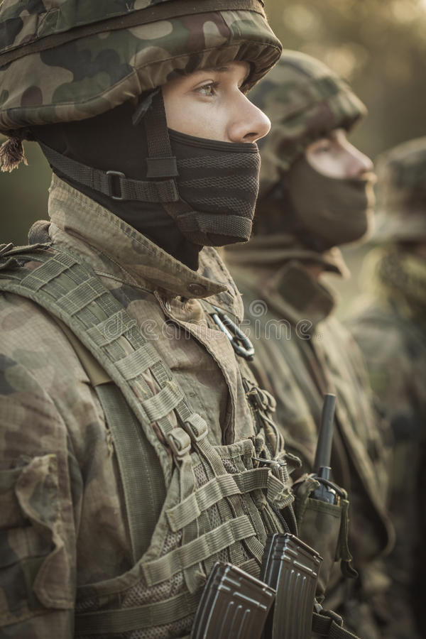 Discipline in an army. Close shot of young soldier in camouflage clothes and helmet standing to attention with other soldiers at the background royalty free stock photography