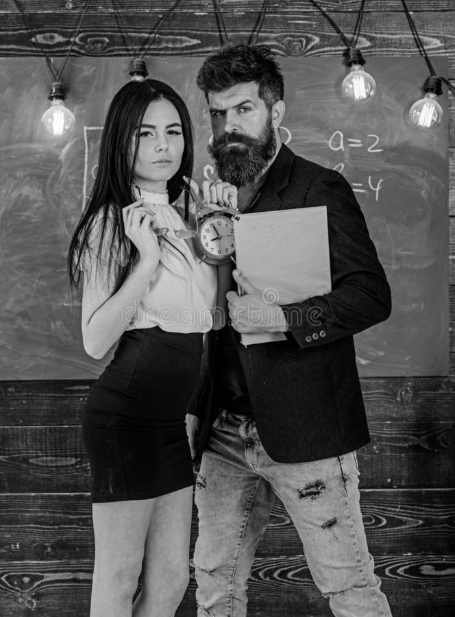Discipline concept. Lady teacher and strict schoolmaster care about discipline and rules in school. Man with beard hold. Book and sexy girl teacher holds alarm stock photos