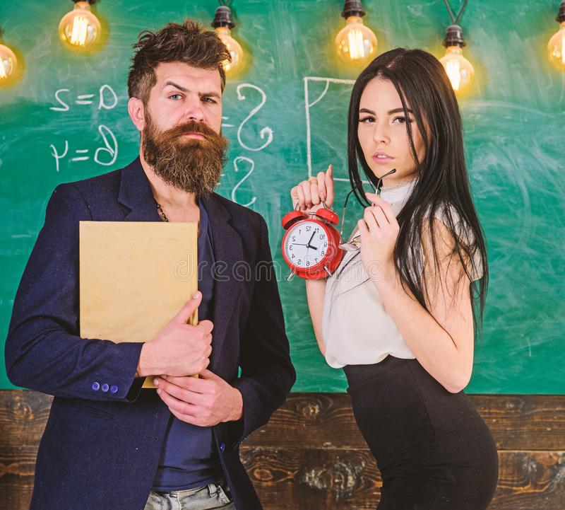 Discipline concept. Man with beard hold book and girl teacher holds alarm clock, chalkboard on background. Lady. Teacher and strict schoolmaster care about royalty free stock image