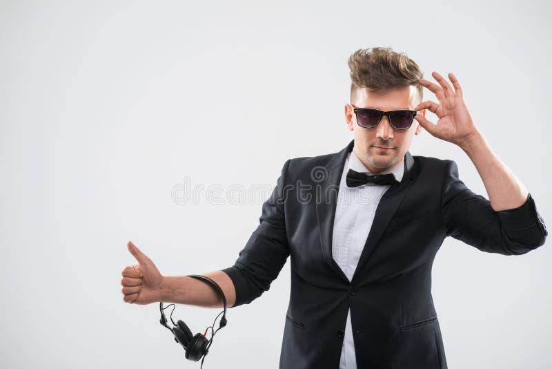 discjockey i smokingen som förbi visar hans tumme upp anseende fotografering för bildbyråer