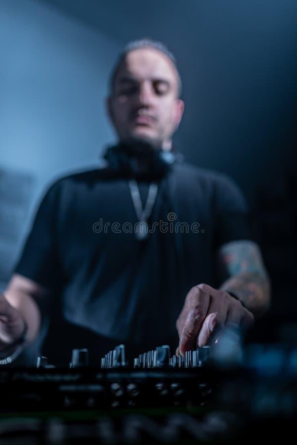 discjockey som spelar hus- och technomusik i en nattklubb Blanda och kontrollera musiken arkivfoton