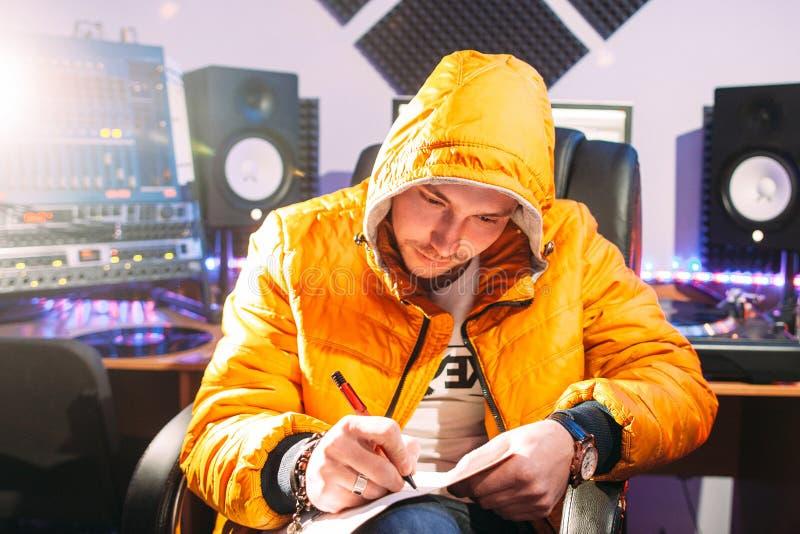 discjockeyn skriver nya lyriska dikter i inspelningstudio royaltyfri foto