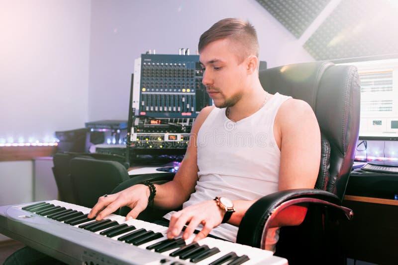 discjockeyn spelar på elektroniskt piano i studion royaltyfri fotografi