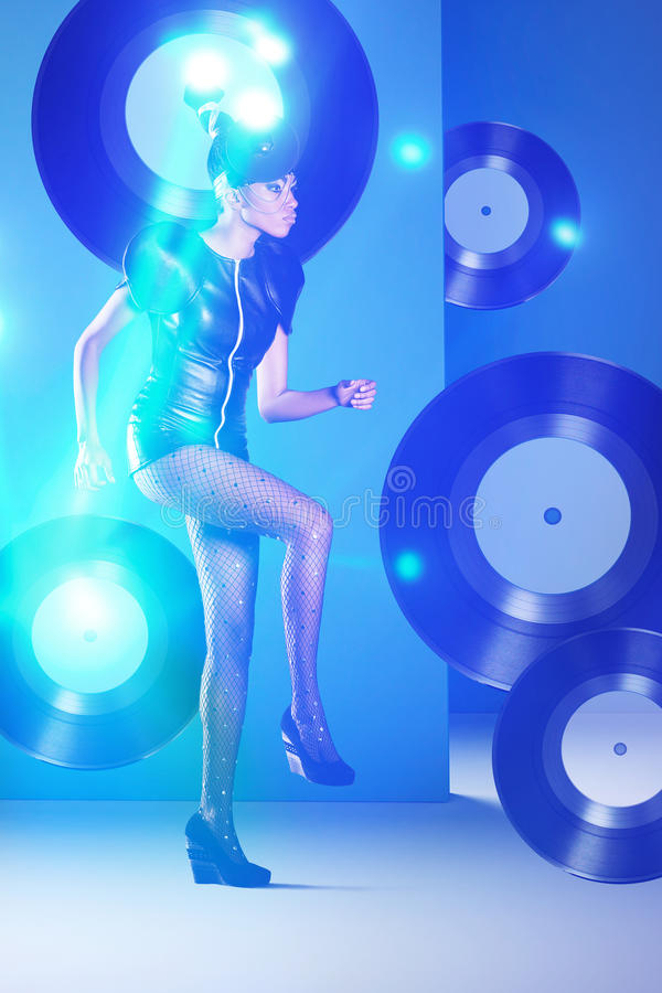 Disco african woman dancing with vinyl records and neon light. Disco african woman dancing with vinyl records royalty free stock photography
