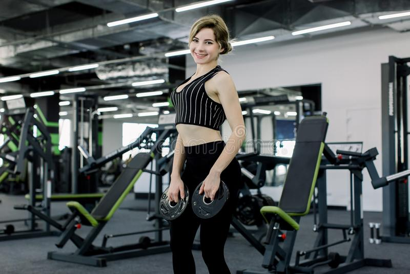 Disco atlético de la tenencia de la mujer joven del barbell y ejercicio en gimnasio imágenes de archivo libres de regalías