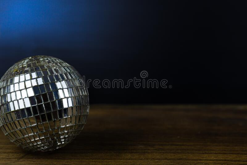 Disco ball on dark wooden floor background stock photography