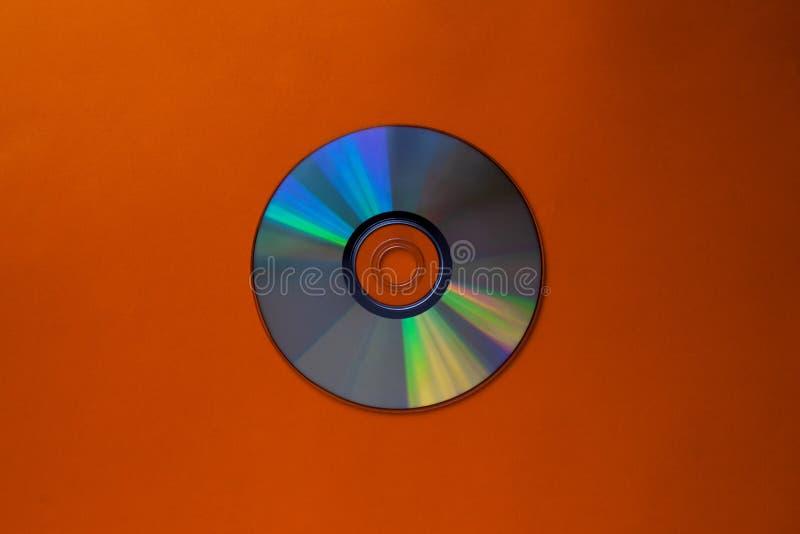 Disco compacto del Cd en una opinión de top anaranjada del fondo con el espacio de la copia foto de archivo