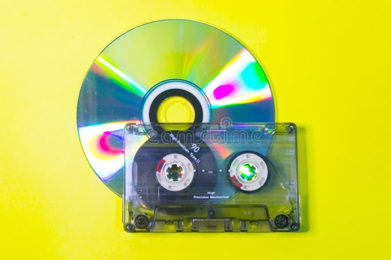 Disco compacto y casete audio en un fondo amarillo fotos de archivo