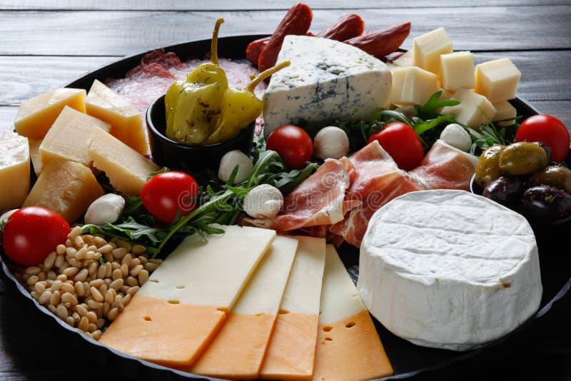Disco de Chesse con el queso, prosciutto, tomate, nueces Consumición sana, lechería, chesses y carne Aperitivo de los Antipasti C fotografía de archivo libre de regalías