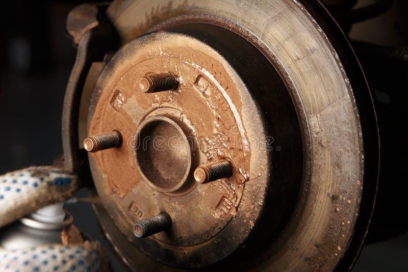 Disco de freio da roda do carro da limpeza do mecânico de carro da corrosão da oxidação na estação do serviço de reparações do au imagens de stock