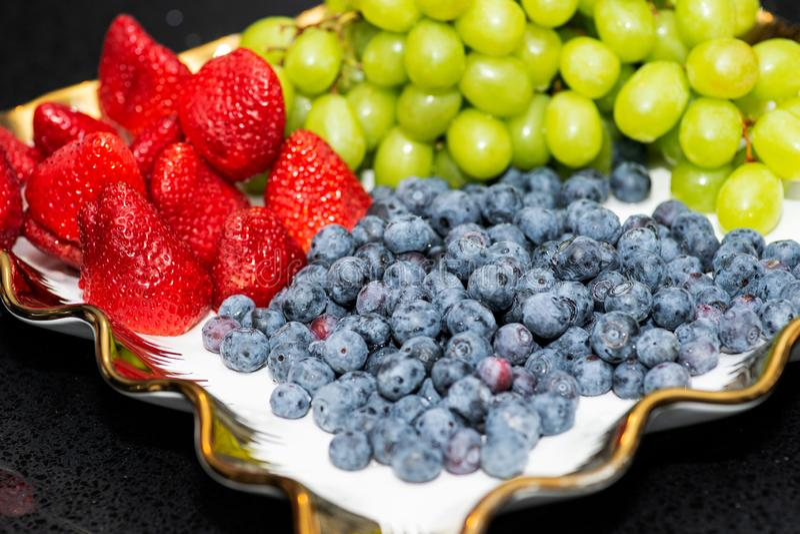 Disco de la fruta fresca con los arándanos orgánicos dispuestos, las fresas, las uvas en la tabla de banquete en el negocio o aco fotos de archivo