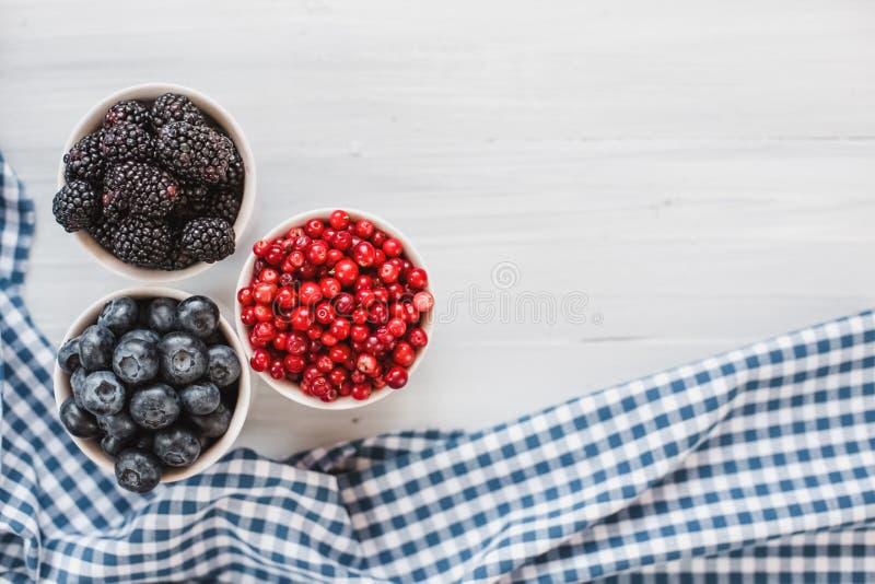 Disco de las bayas con la tabla de madera roja orgánica fresca del arándano, del arándano y de la zarzamora, visión superior fotografía de archivo