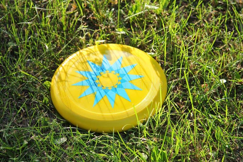 Disco de vuelo plástico del disco volador que miente en la hierba en el parque Juguete del ` s de los niños para los juegos al ai fotografía de archivo