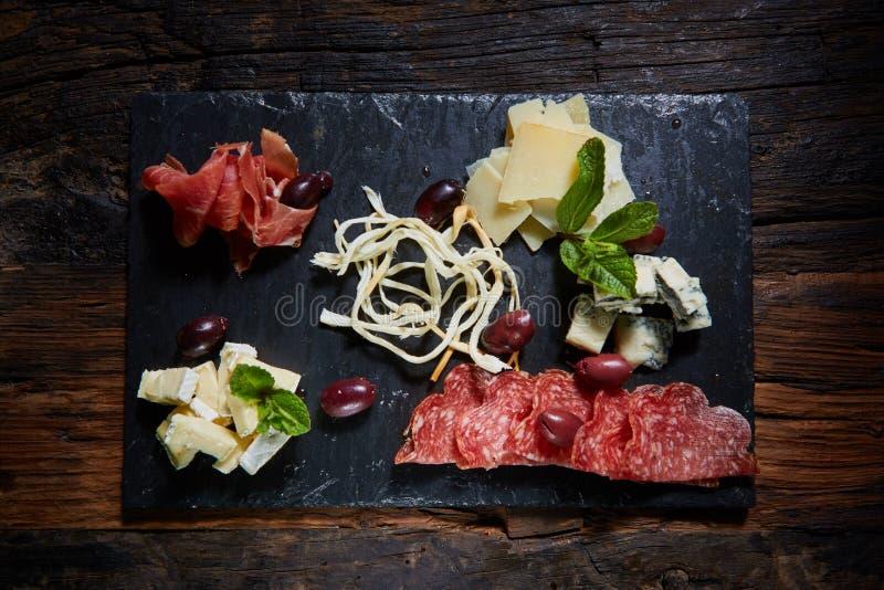 Disco del formaggio e del salame con le erbe fotografie stock