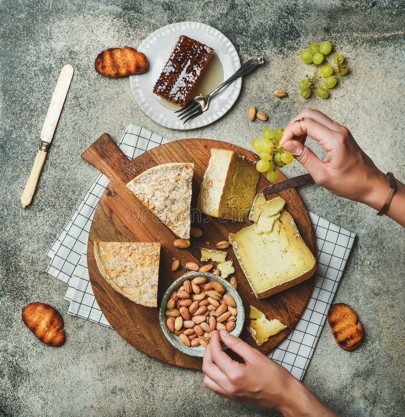 Disco del queso con las manos femeninas que alcanzan a la comida foto de archivo