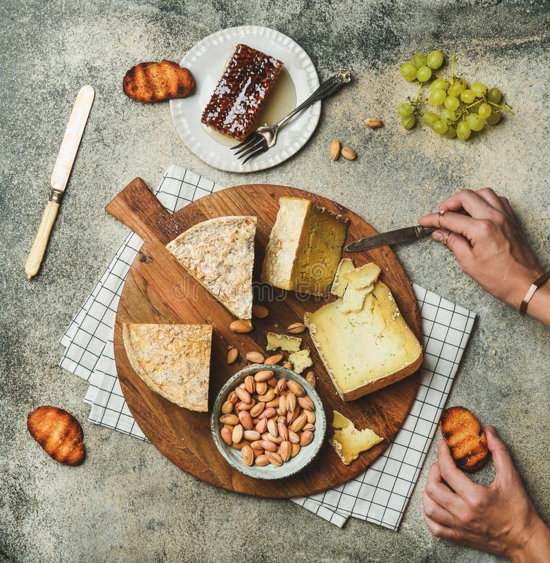 Disco del queso con las manos femeninas que alcanzan a la comida, plano-endecha imagen de archivo libre de regalías