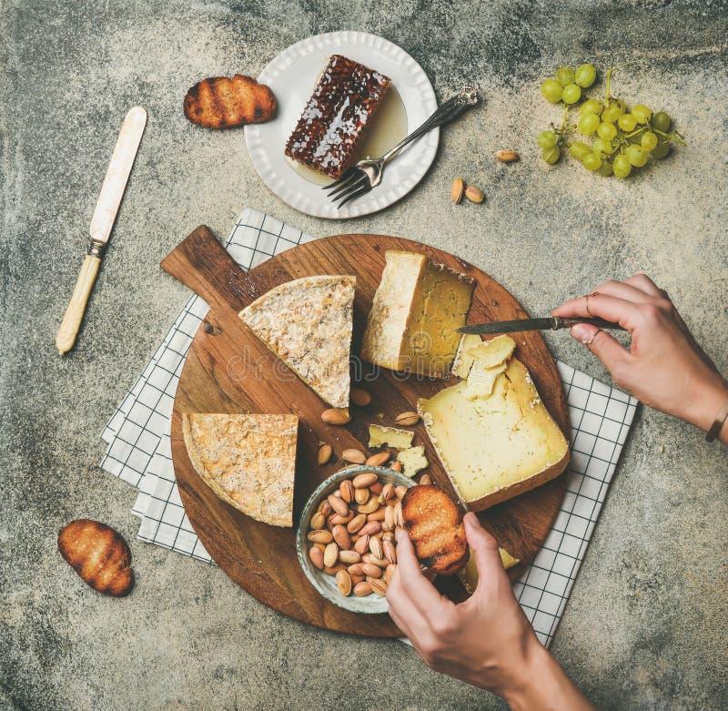 Disco del queso con las manos femeninas que alcanzan a la comida, visión superior fotografía de archivo libre de regalías