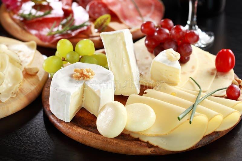 Disco del queso y del salami con las hierbas imágenes de archivo libres de regalías