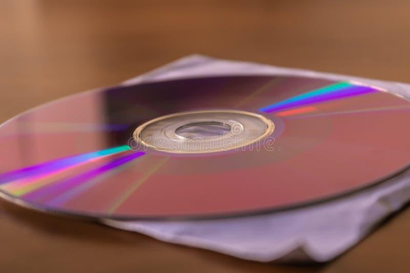 Disco di DVD del CD sul primo piano bianco del contenitore di copertina di carta fotografie stock libere da diritti