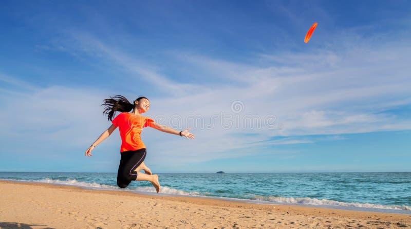 Disco di volo asiatico del gioco della ragazza sulla spiaggia fotografia stock