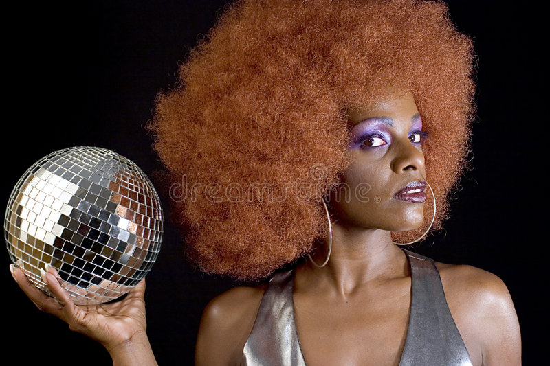 Disco Diva 1. Attractive black woman wearing purple eye makeup and holding a disco ball royalty free stock image